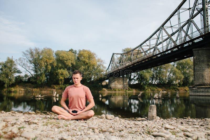 在老桥梁附近供以人员在河岸的实践瑜伽 免版税库存照片