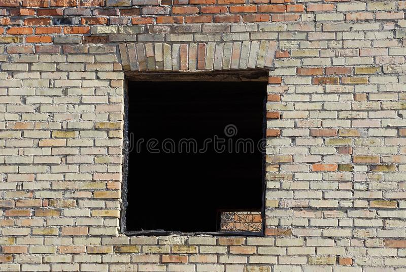 在老棕色砖墙上的黑空的窗口 免版税图库摄影