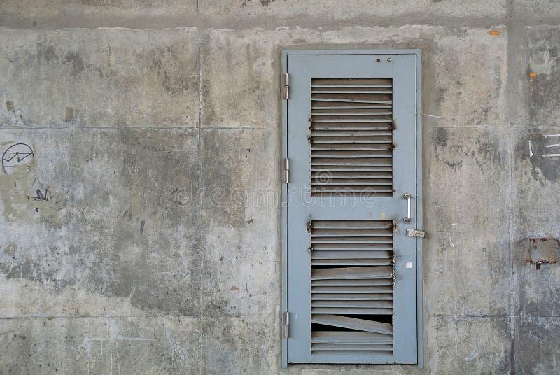 在老混凝土墙上的难看的东西灰色金属门 库存图片