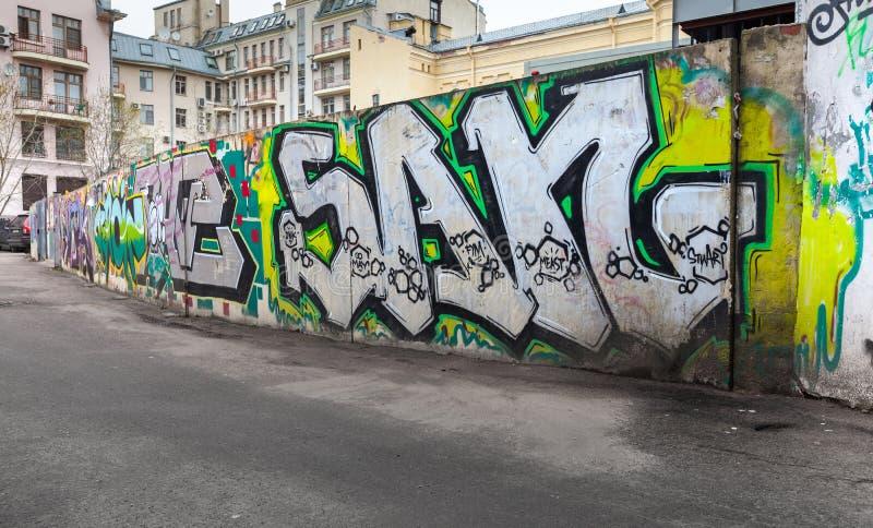 在老灰色具体篱芭的五颜六色的混乱街道画 库存照片