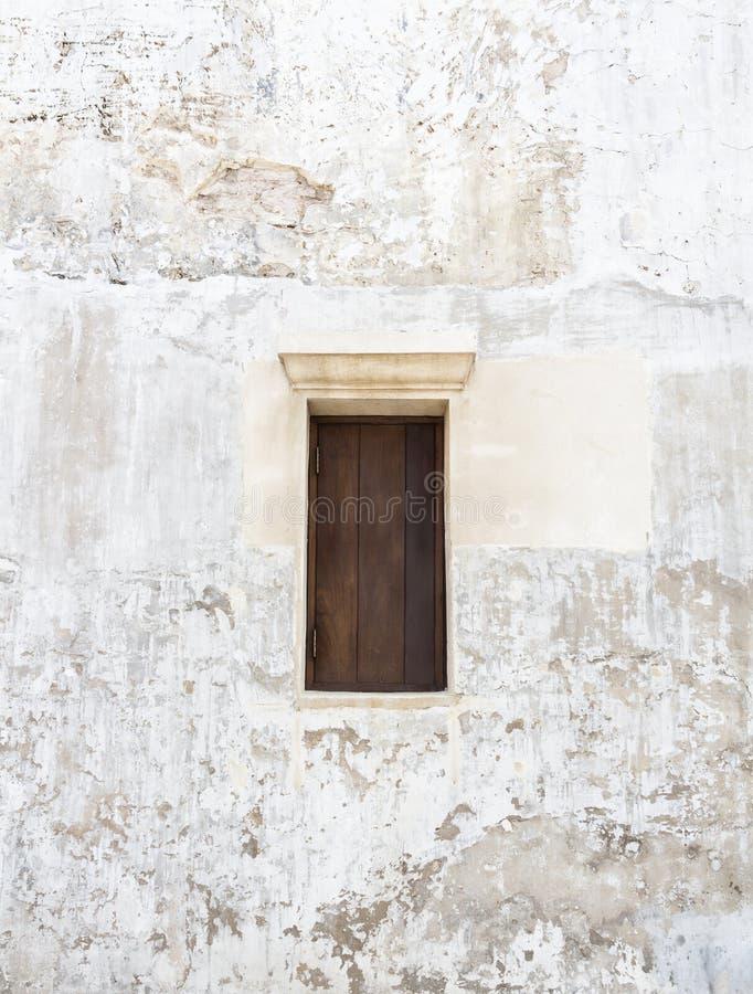 在老灰色水泥墙壁上的木窗口有破裂的颜色的 Vint 免版税库存图片
