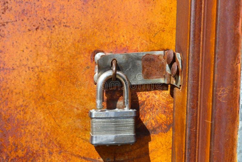 在老生锈的门的银色挂锁留给开锁任何人可能得到橙色和棕色铁锈的地方充满活力的颜色 免版税库存照片