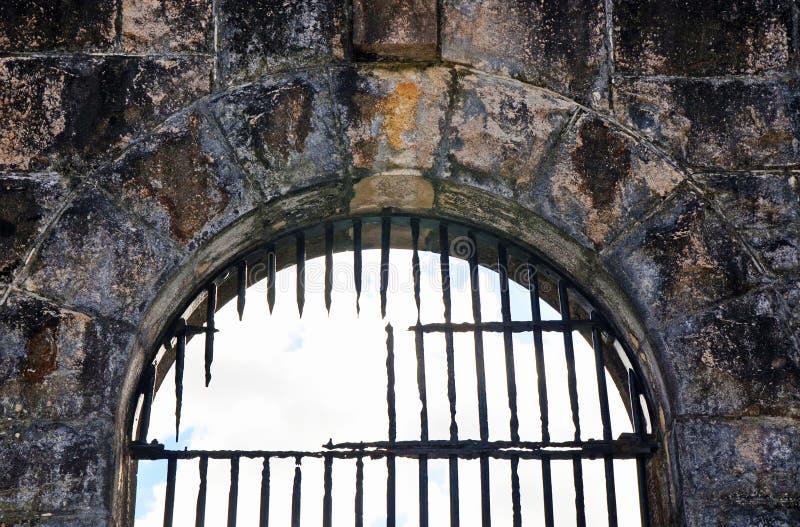 在老监狱(监狱)的残破的生锈的钢棍成拱形窗口 免版税图库摄影