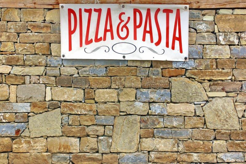 在老石墙上的意大利食物标志 库存图片