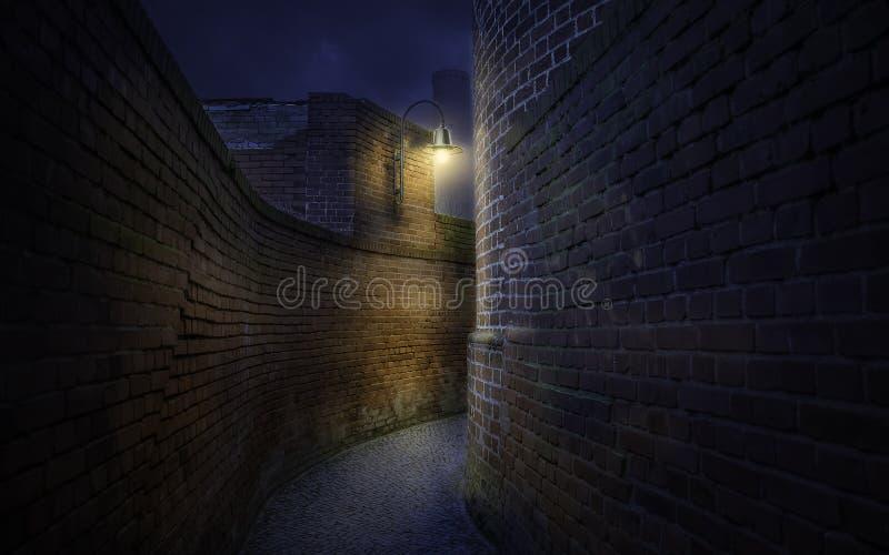 在老砖墙中的弯曲的路在晚上 免版税库存照片