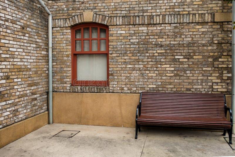 在老砖墙和大木椅子上的玻璃窗 图库摄影