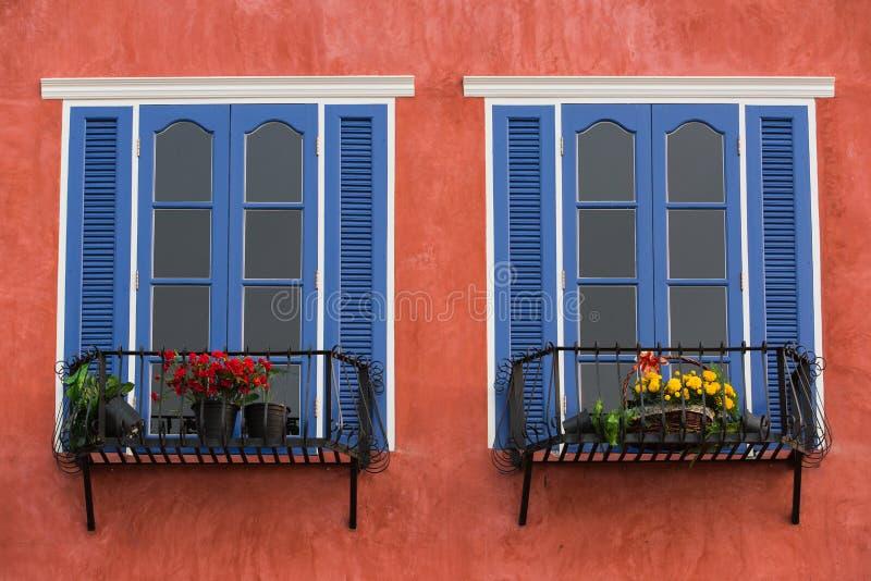 在老红色灰泥墙壁上的双装饰蓝色窗口 库存图片