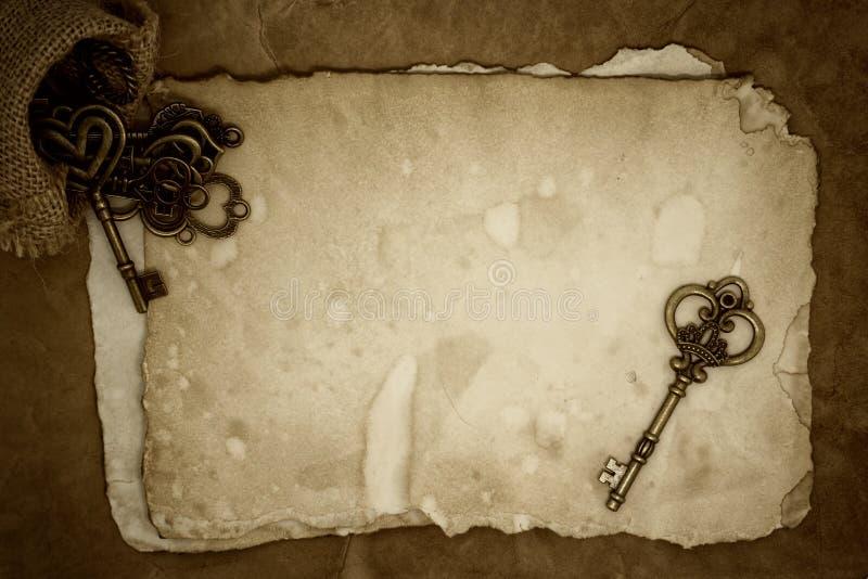 在老纸背景的老钥匙 库存图片