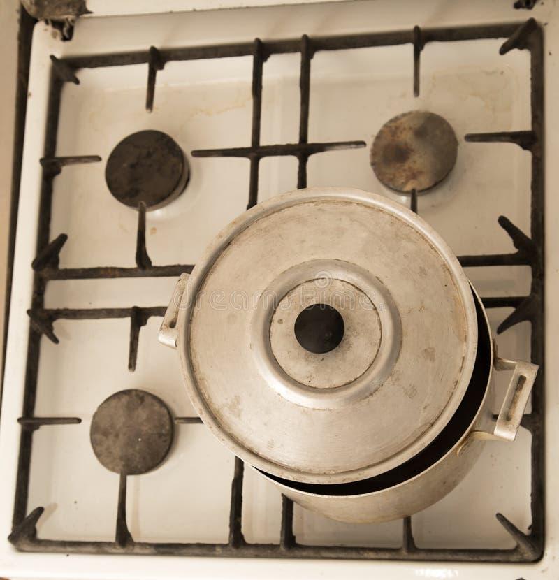 在老肮脏的煤气炉的铝平底锅 免版税库存照片