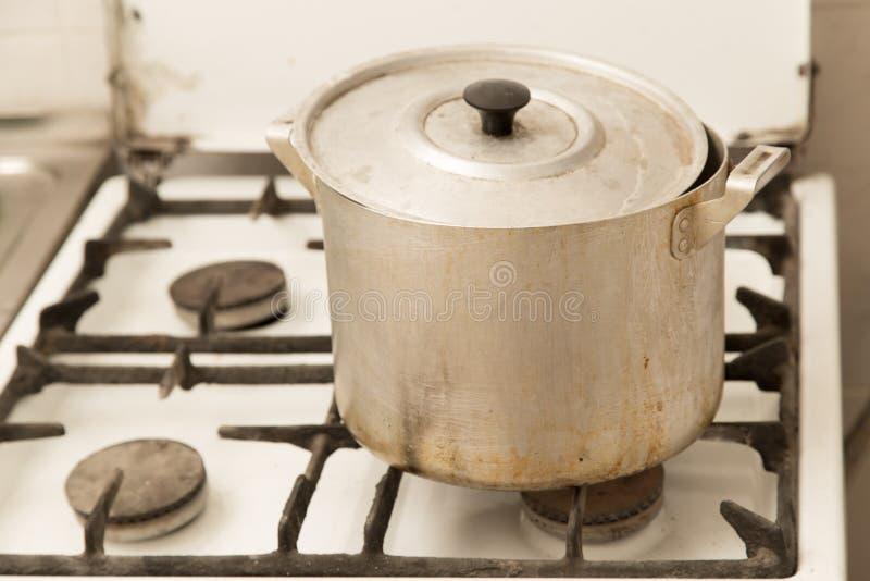 在老肮脏的煤气炉的铝平底锅 库存图片