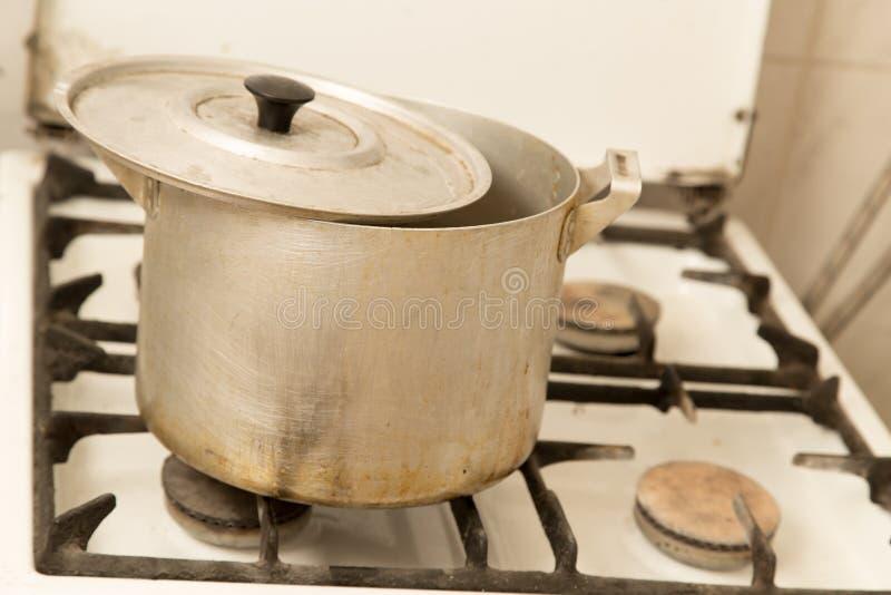 在老肮脏的煤气炉的铝平底锅 免版税库存图片