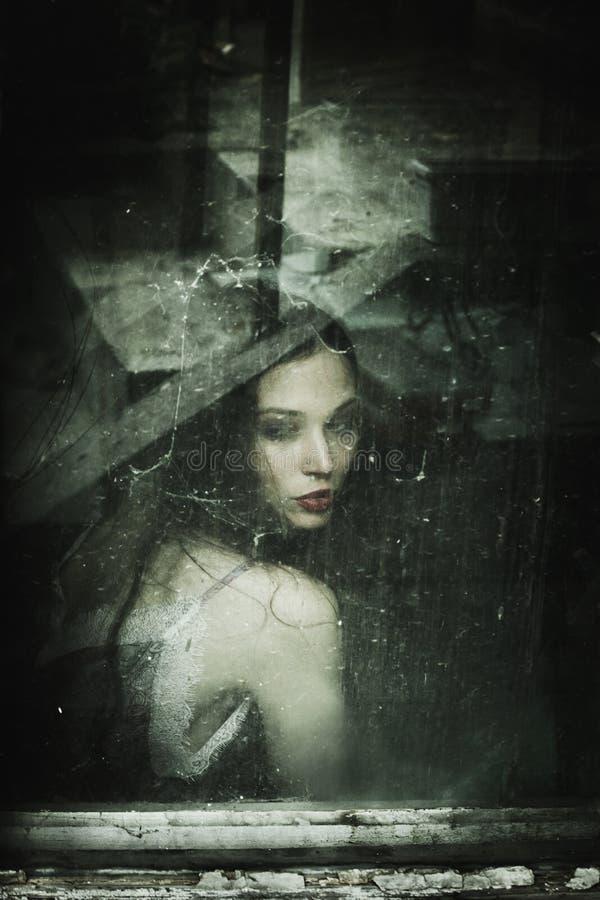 在老肮脏的窗口后的肉欲的少妇画象 库存照片