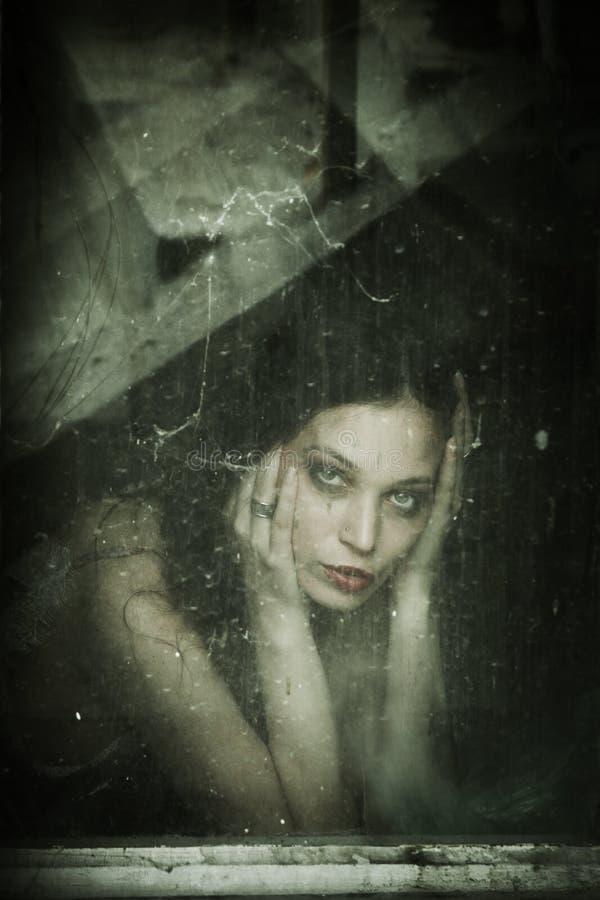 在老肮脏的窗口后的肉欲的少妇画象 免版税库存图片