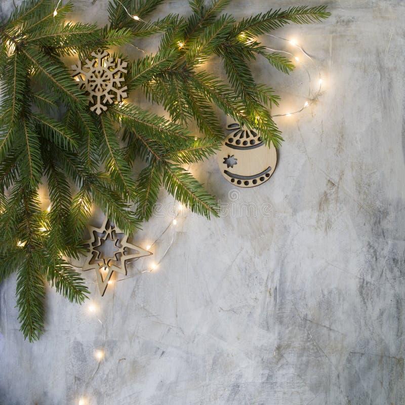 在老葡萄酒板的圣诞卡片与分支圣诞树、木雪花和球和发光光 新年度 库存图片
