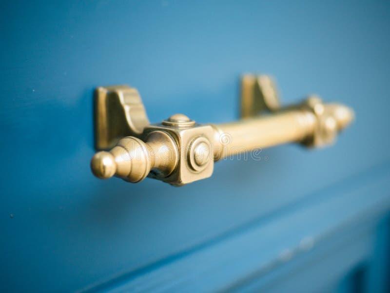 在老蓝色木门的葡萄酒古色古香的门把手 库存图片