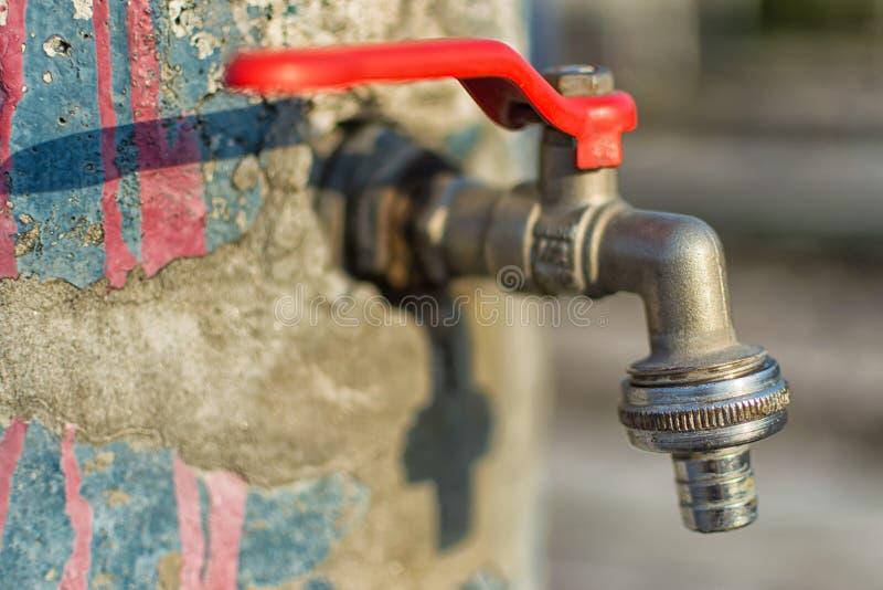 在老蓝色被绘的墙壁上的龙头 红色把柄水龙头室外背景 概念节约水 库存照片