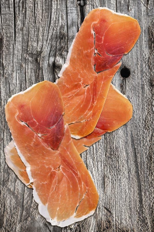 在老被打结的破裂的木庭院表上的被治疗的猪肉火腿切片 库存图片
