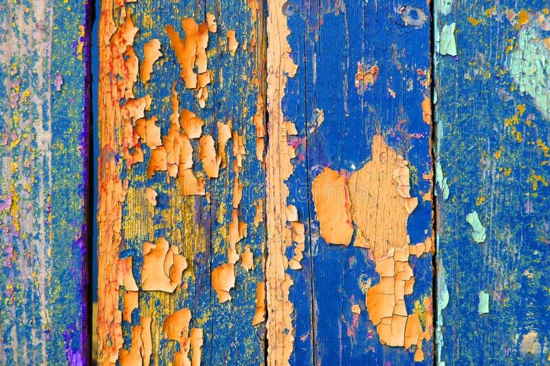 在老被风化的蓝色和橙色木头-织地不很细背景的削皮油漆 图库摄影