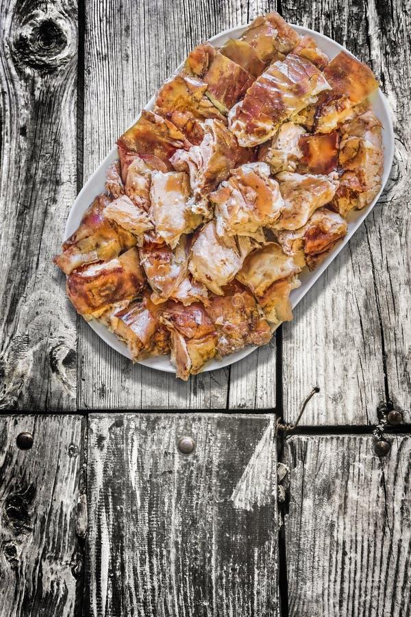 在老被风化的破裂的木庭院表上设置的满盘唾液烤猪肉肉切片 免版税库存图片