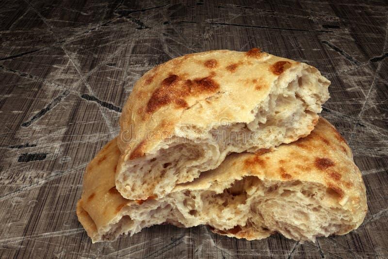 在老被风化的破裂的片状木庭院表上设置的新近地被烘烤的国内皮塔面包大面包被撕毁的一半 图库摄影
