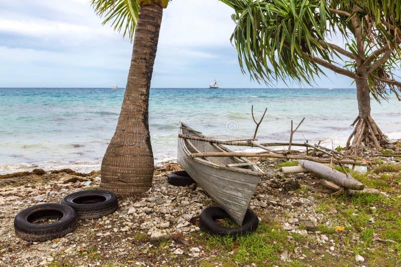 在老轮胎上面的传统玻利尼西亚舷外浮舟在岩石 库存图片