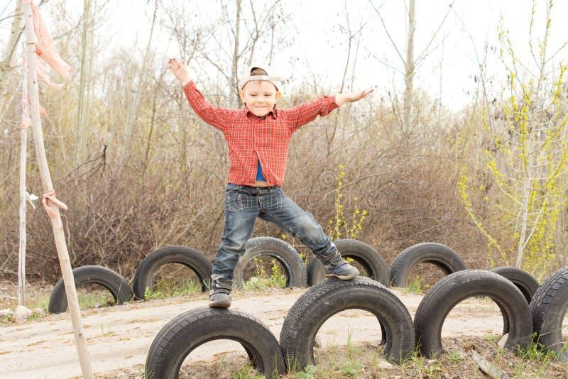 在老轮胎平衡的逗人喜爱的小男孩 库存照片