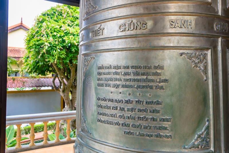 在老金属响铃的宗教文本在一座塔在大叻越南 库存图片