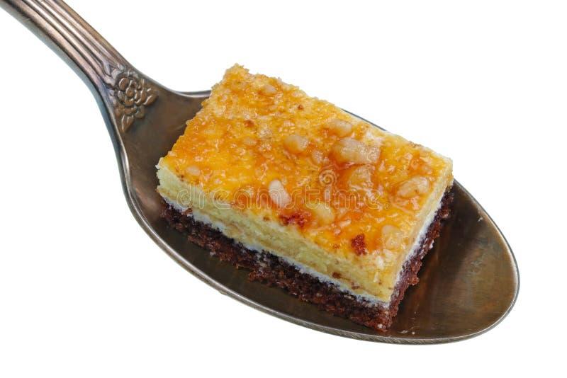 在老金黄匙子有小堆食物-切片蛋糕用胡说的被隔绝的蜂蜜和巧克力 免版税库存照片