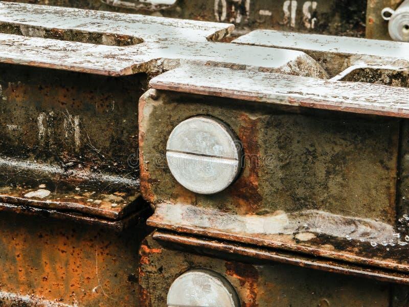 在老锌生锈的难看的东西紧固的带帽螺栓螺丝镀锌了波状钢 剥落的裂化的土气老金属背景和铁锈 免版税库存图片
