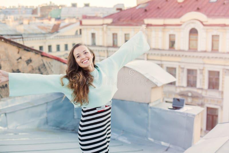 在老镇的屋顶的晚上走一个美丽的女孩的画象 自由的概念 她站立与 免版税图库摄影