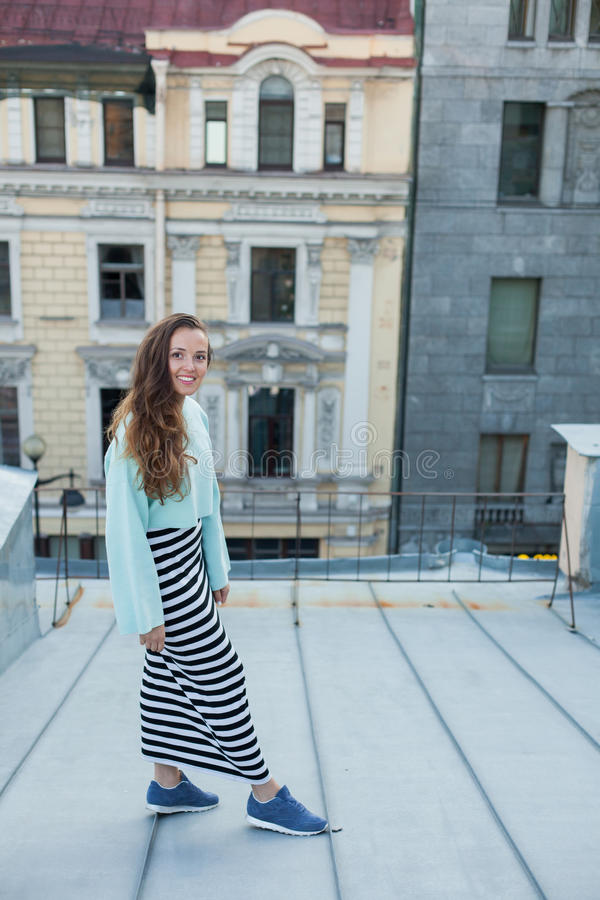 在老镇的屋顶的晚上走一个美丽的女孩的画象 自由的概念 免版税库存图片