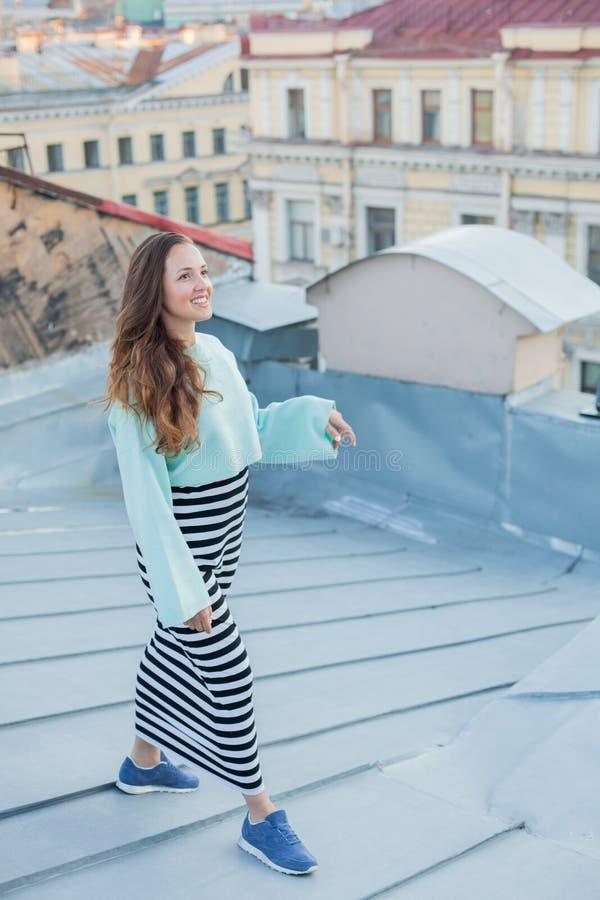在老镇的屋顶的晚上走一个美丽的女孩的画象 自由的概念 免版税库存照片