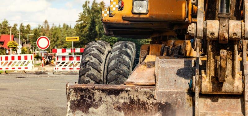 在老黄色挖掘机的机器的细节,路关闭了标志,建筑过程中的背景 长跑训练概念横幅 免版税库存图片