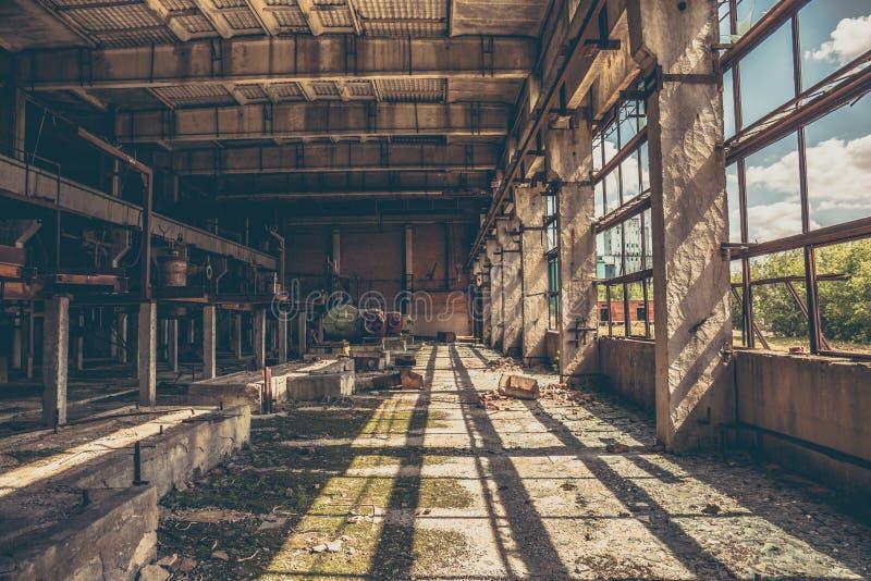 在老黑暗的难看的东西工厂厂房里面的被放弃的工业蠕动的仓库 库存图片
