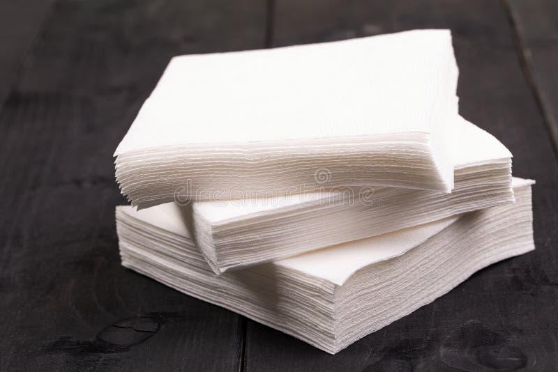 在老黑木桌上的白皮书餐巾 库存图片