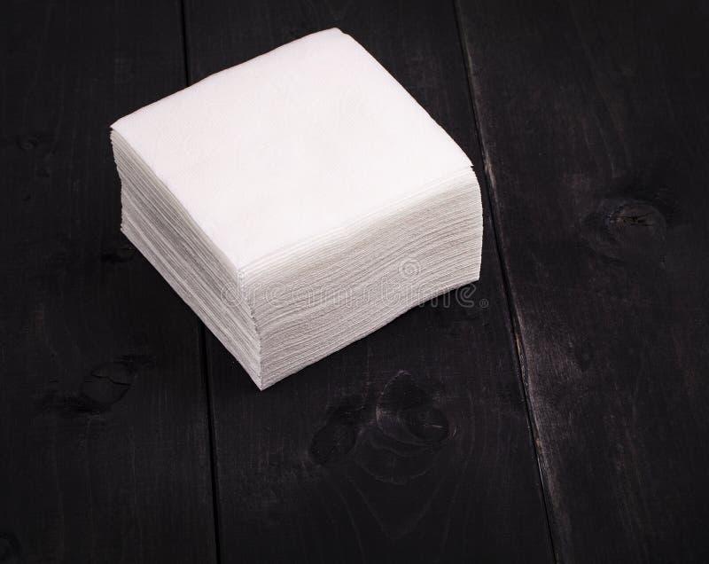 在老黑木桌上的白皮书餐巾 免版税库存图片