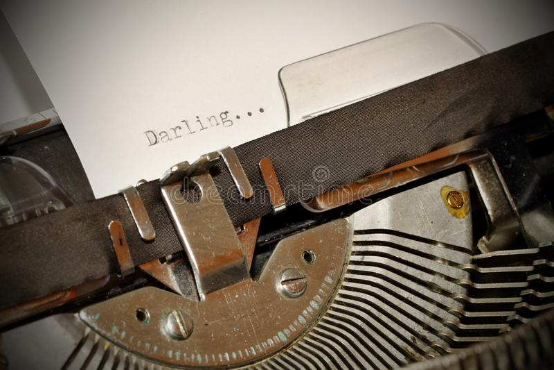 在老黑typwriter键入的亲爱的词 免版税库存照片