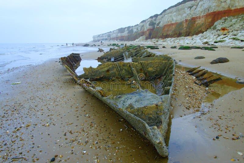在老Hunstanton峭壁下的老拖网渔船残骸 免版税库存照片