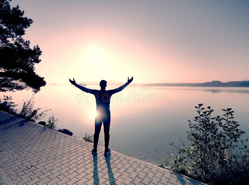 在耐力训练的公长跑运动员在山湖 免版税库存照片