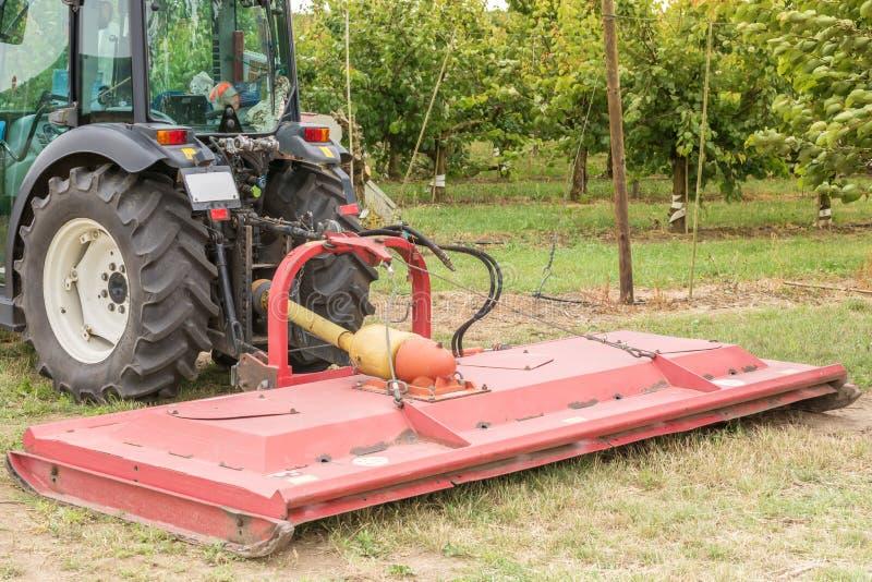 在耕种果树园的一台小拖拉机的转台式刈草机 库存图片