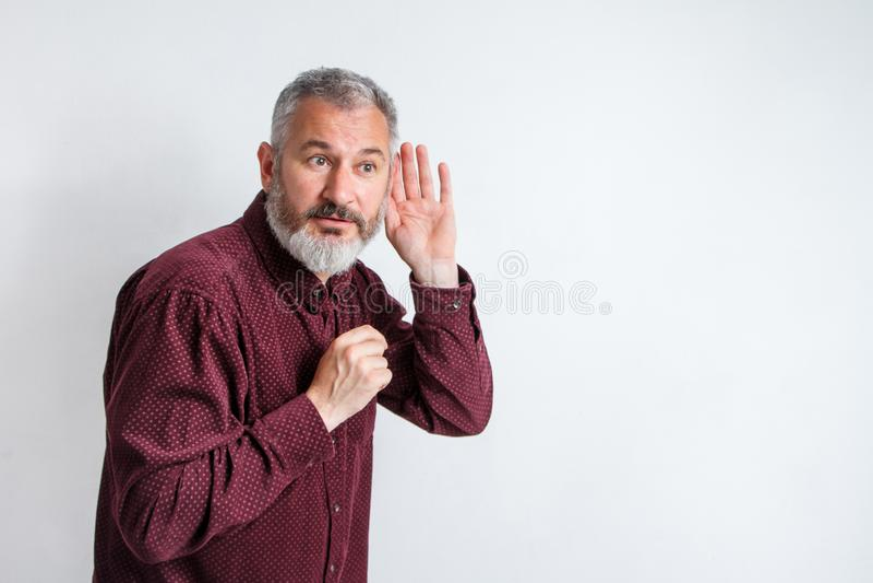 在耳朵更好听见的,窃听和spyingblems附近的人有胡子的行家举行手 免版税库存照片