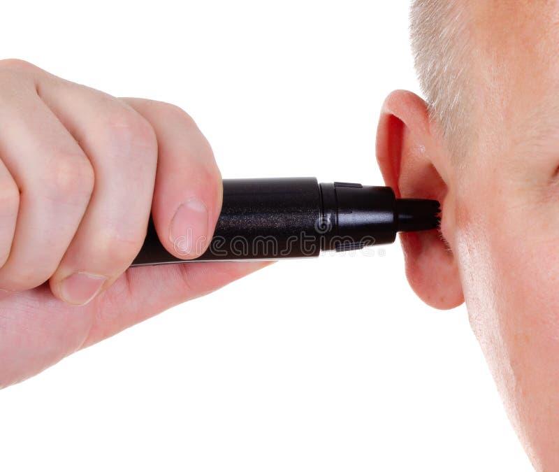 在耳朵的头发整理者在被隔绝的背景 r ( 整理者广告 免版税库存图片