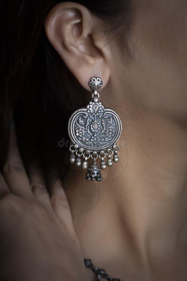在耳朵的妇女佩带的银色耳环 库存图片