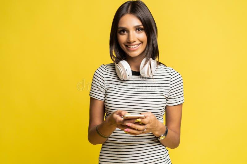 在耳机和使用智能手机的微笑的妇女听的音乐在黄色背景 库存照片