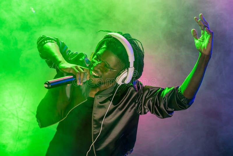 在耳机的专业非裔美国人的俱乐部DJ唱歌与话筒的 库存照片