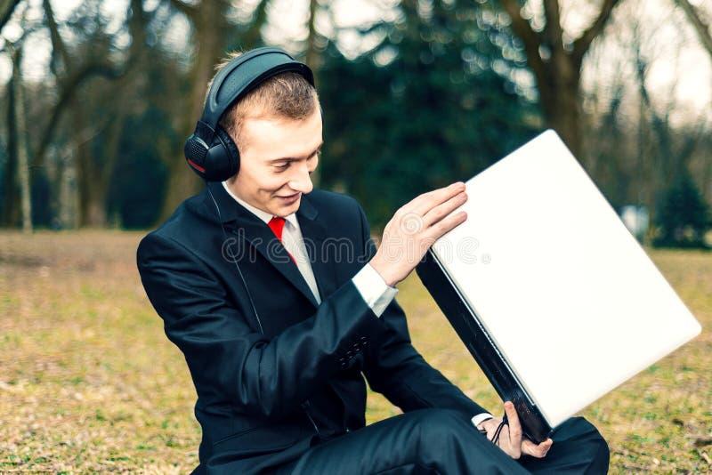 在耳机的商人谈话在膝上型计算机 互联网通信 一套衣服的年轻人在自然 自由职业者,遥远 库存图片