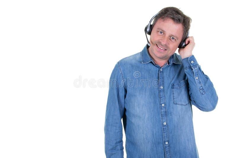 在耳机的愉快的中间年迈的商人在与旁边拷贝空间的白色背景 免版税图库摄影