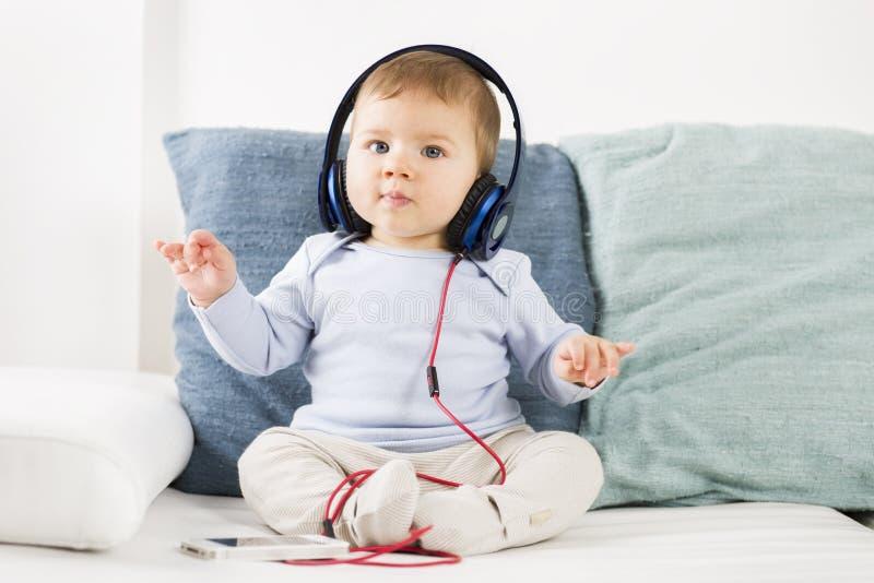 在耳机的甜男婴听的音乐在举办假定 库存图片