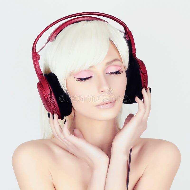 在耳机的秀丽少妇听的音乐 库存图片