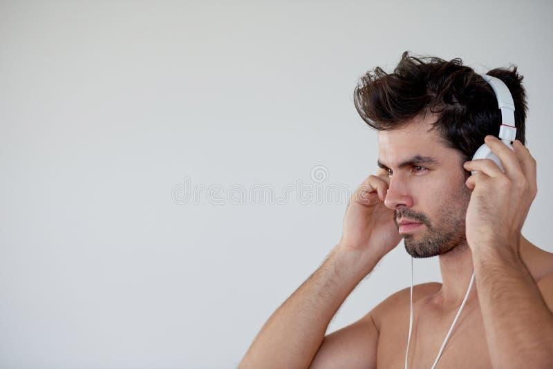 在耳机的英俊的年轻人听的音乐 库存照片